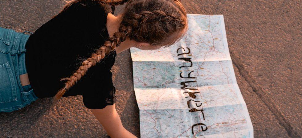 """Mädchen, das eine Landkarte studiert, auf der in fetten Buchstaben """"anywhere"""" steht"""